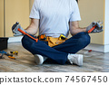 Cropped shot of young handyman holding a hammer and an adjustable wrench in his hands while meditating, sitting in Lotus pose on the floor indoors 74567450