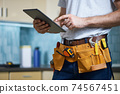 Cropped shot of young repairman wearing a tool belt with various tools using digital tablet while standing indoors 74567451