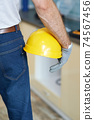 Close up shot of professional repairman holding a helmet while standing indoors 74567456