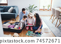 Parents with small daughters indoors at home, packing for summer holiday. 74572671