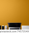 Flat lay top view office desk working space with laptop and office supplies on orange background. 74573549
