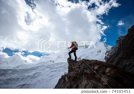 Woman hiker enjoy the view on winter mountain top cliff edge 74585451