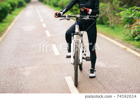 Cyclist use smartphone when riding mountain bike on forest trail 74592014