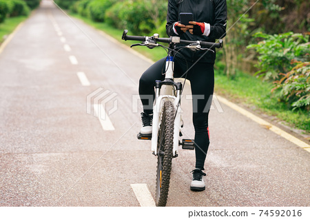 Cyclist use smartphone when riding mountain bike on forest trail 74592016
