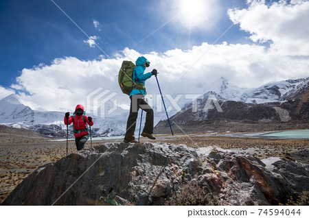 Two women hikers hiking  in winter mountains 74594044
