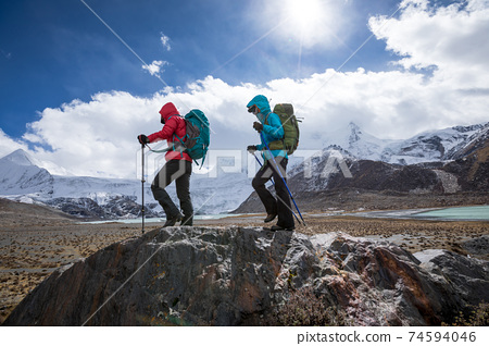 Two women hikers hiking in winter high altitude mountains 74594046