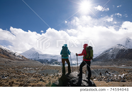 Two women hikers hiking in winter high altitude mountains 74594048