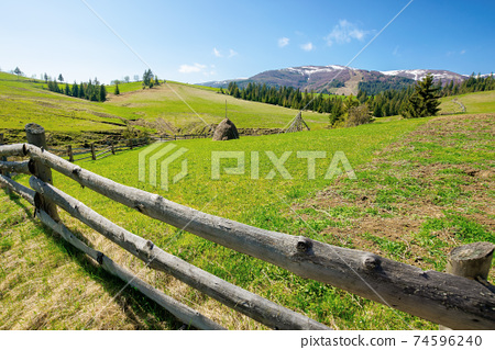 mountainous rural landscape in spring. haystack on a grassy field behind the wooden fence on rolling hills. snow capped ridge in the distance. beautiful countryside scenery on a bright sunny day 74596240