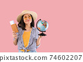 Asian woman holding passport with boarding pass and globe 74602207