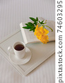 Cup of tea with a book on a white tray with a yellow flower on a white bed 74603295
