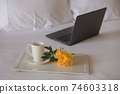 Cup of tea with a yellow flower on a white bed next to laptop.  74603318