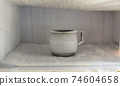 Stainless steel drinking water glass in freezer of a refrigerator. Ice buildup inside of a freezer walls. 74604658