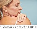 Rear view of a mature woman touching her shoulder with soft skin while standing against blue background 74613810