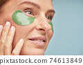 Close up portrait of a beautiful adult lady using eye patches while standing against blue background 74613849
