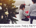 Girl opening a Christmas present 74617877