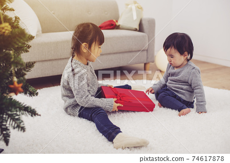 Girl opening a Christmas present 74617878