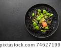 Pasta spaghetti squid Ink with sauce Pesto in black bowl on black. 74627199