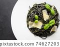 Black pasta spaghetti squid Ink with sauce Pesto in black bowl on black. 74627203