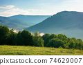mountain meadow in morning light. countryside springtime landscape with valley in fog behind the forest on the grassy hill. fluffy clouds on a bright blue sky. nature freshness concept 74629007