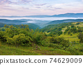 mountainous countryside scenery at dawn. distant valley full of fog in summer. plants and trees on the hill. beautiful landscape with clouds on the sky 74629009