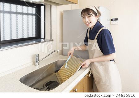 房屋清潔女工刷燃氣灶呼吸機的過濾器 74635910
