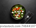 Salad with spinach, cherry tomatoes, onion and Mozzarella on black stone background. Top view. 74644107