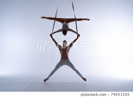 Aerial straps duo wearing white costume on white background doing performance  74651585
