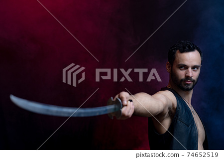 Muscular Man posing with long sword isolated on black and smoked background 74652519
