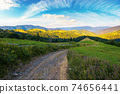 rural landscape in mountains at summer sunrise. country road through grassy pasture winding down in to the distant valley. clouds on the blue sky above the ridge in the distance 74656441