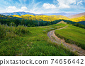 rural landscape in mountains at summer sunrise. country road through grassy pasture winding down in to the distant valley. clouds on the blue sky above the ridge in the distance 74656442