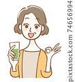 Middle-aged woman holding green juice and signing OK 74656994