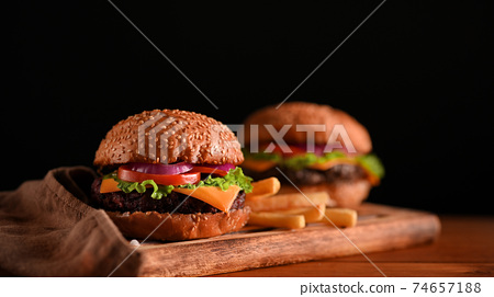 Close-up view of delicious grilled beef burgers served on wooden tray on the table 74657188