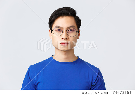 Lifestyle, people emotions and beauty concept. Close-up of asian man in glasses with stylish haircut looking at camera with normal, calm expression, standing grey background 74673161