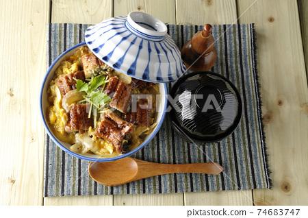 鳥瞰的一套鰻魚碗,湯和木勺鰻魚片在餐墊上 74683747