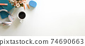 Workspace is surrounding by headphones, coffee, flower pot and accessories. 74690663