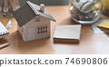 A house model is putting on a wooden working desk surrounded by saving money and personal equipment. 74690806