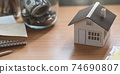 A house model is putting on a wooden working desk surrounded by saving money and personal equipment. 74690807