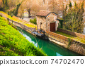 ancient structure of the river lock along the canal surrounded by thick vegetation 74702470