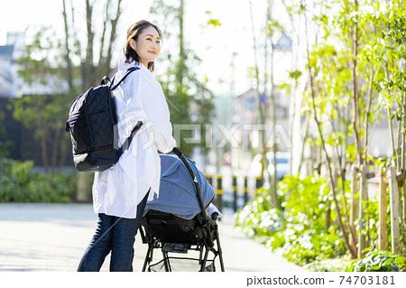 在嬰兒推車旅行的年輕女子 74703181
