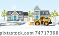 Snow plow truck cleaning snows area streets at village home. 74717398
