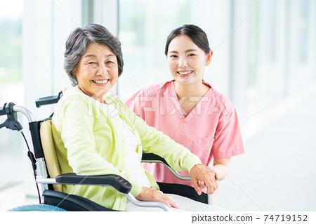 휠체어 노인 여성과 개호 직원 74719152