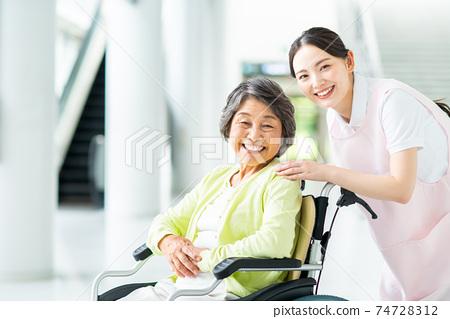 휠체어 노인 여성과 개호 직원 74728312