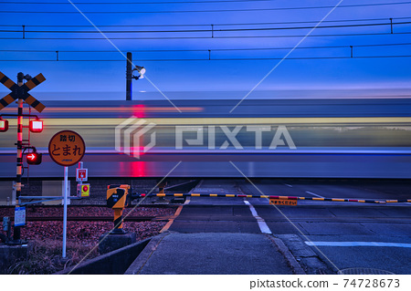 快速的火車趕回家,在黃昏時分穿過散打的鐵路道口 74728673