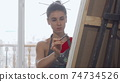 Elegant woman painting a picture at the workshop 74734526
