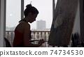 Silhouette of a female painter working at her studio 74734530