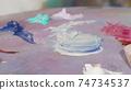 Unrecognizable female artist mixing paint on a palette 74734537