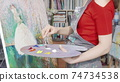 Cropped shot of a female artist mixing paint on her palette while drawing 74734538