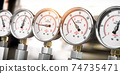 Row of gas pression gauge meters on gas pipeline. Gas extraction, production, delivery and supply concept. 74735471