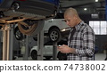 Handsome African man using smart phone at the garage 74738002