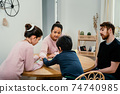 Mixed family playing with board game together at the table 74740985
